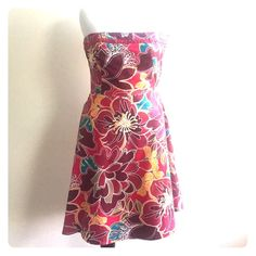 Floral Strapless Dress Feel festive in this multi pink toned floral strapless dress. Accented with a fuchsia beaded ribbon at the bust line, an A-line bottom finishes the dress. Amanda Smith Dresses Strapless