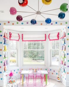 Rainbow playroom features polka dot rainbow wall decals, a rainbow sticker by Sazerac Stitches, lucite chairs, and rainbow book shelves. Rainbow Room Kids, Rainbow Wall, Kids Room Lighting, Colorful Playroom, Baby Boy Nursery Decor, Chandelier, Rainbow Decorations, Colorful Interiors, Modern