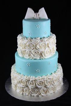 blue wedding cake with white rosettes