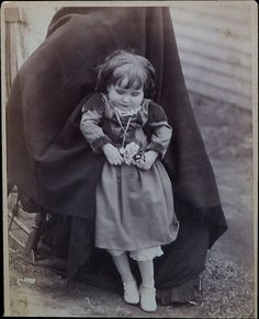 Post mortem of a little girl with a flower in her hand, held up in standing position by a hidden person. Cabinet card from Villisca, Iowa about 1890