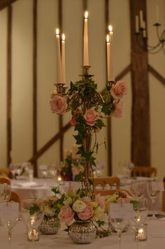 Upwaltham Barn, tables decorated with silver candelabras.  These have been lightly covered with trailing ivy and studded with roses.  Roses in silver speckled vases bring colour down onto the white cloth.