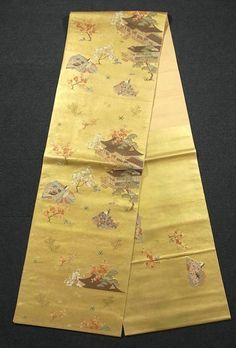 This is a graceful Fukuro obi with a design of noble, royal cart and flowers, which is woven on the tranquil gold background