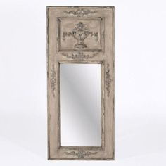 Draw guests into your home by displaying a classic French-carved tremeau mirror featuring a hand-painted natural gesso grey finish just inside the entryway. The mirror is antiqued in a spotted finish giving it an aged appeal.