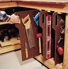 Металлические вертикальные перегородки с отверстиями и крючками для упорядоченного хранения инструментов.