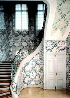 Antique Dutch Delft Tiles surround a curved staircase via Atticmag