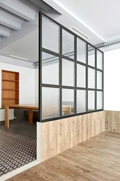 Apartment in Barcelona with a sequence of rooms lined in patterned tiles, micro-cement, marble and wood