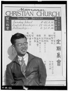 Taken in 1943 by Ansel Adams, Tatsuo Miyake, a divinity student at Manzanar sits in front of a sign for church services given in English and Japanese.