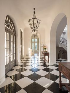 Large spacious entryway with archways and white and black tiled floor | Bradley E Heppner