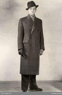 """""""Herrkonfektion, Menswear, ytterplagg, Nordiska Kompaniet"""". Man iklädd överrock, hatt och handskar. Fotograf: Studio Sun, ca 1930-1935"""