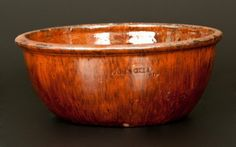 """Sold $375 Fine Glazed Redware Bowl, Stamped """"JOHN BELL / WAYNESBORO,"""" PA origin, third quarter 19th century, with rounded sides and semi-rounded rim molding, the entire surface covered in a heavy lead glaze. Interior shoulder decorated with manganese highlights, the entire exterior surface further decorated with manganese streaks. Impressed """"JOHN BELL / WAYNESBORO"""" below rim. Thin, approximately 2"""" crack from rim. In-the-firing tripod marks"""
