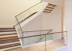Simple and elegant. Frameless clear glass laminated glass staircase panels topped with a slim wooden handrail have been used in place of traditional newel posts and spindles for this large light staircase – Stock image Stairs With Glass Panels, Glass Stairs, Glass Handrail, Glass Balustrade, Laminated Glass, Newel Posts, Wooden Tops, Safety Glass