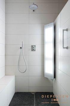 Een ruime douche met inbouwkranen en een sunshower.