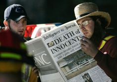 """Two men read a newspaper with the headline """"Death of Innocents"""" while standing at a roadblock near the scene of the shooting at the one-room Amish schoolhouse Tuesday, Oct. 3, 2006 in Nickel Mines, Pa. Officials said a milk truck driver identified as Charles Carl Roberts IV entered the schoolhouse, let the boys and adults go free, tied up the girls and shot them execution style before committing suicide. Five girls died."""