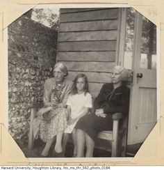 Virginia Woolf, Virginia Richards and Noel Olivier sitting on a bench outdoors in front of the writing lodge at Monk's House