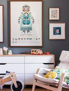 quarto infantil com móveis de madeira clara e quadros coloridos