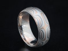 Contemporary mokume wedding band 8mm wide in etched mokume of 14K palladium white gold, 14K red gold and sterling silver in star pattern.