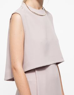 Simple and minimal textured sleeveless top from Kaarem. Features zip closure at the shoulders, a high-low hem, and a simple, clean styling.   •Round neck sleeveless top •Textured feel •Shoulder zip closure •High-low hem  •100% Polyester