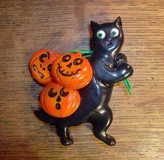 Carved Bakelite Halloween brooch of a black cat carrying three pumpkins (pretty much my dream vintage brooch!). #Bakelite #jewelry #black_cats