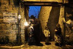 Иудей в Иерусалиме зажигает свечу в светильнике в восьмой и последний день праздника Хануки - праздника чуда.