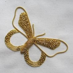 This glistening butterfly design combines a range of goldwork embroidery techniques on a background of calico fabric. With all of the fabrics, threads, needles