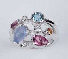 Anel de ouro branco, calcedoni, topazio azul, turmalina rosa, com 0,12ct de brilhantes e 11,9g. Assi