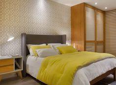 QUARTO CASAL   Papel de parede amarelo geométrico da Guilha. Cama, armários e divisória ripada, todos da Canto de Dormir (Foto: MCA Estúdio/Divulgação )