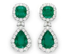 A PAIR OF EMERALD AND DIAMOND EAR PENDANTS Each suspending a detachable pendant, set with a pear-shaped emerald, weighing approximately 10.82 and 14.48 carats, within a graduated circular-cut diamond surround, joined by a pear-shaped diamond double-link, from a surmount of similar design, set with a cushion-cut emerald, weighing approximately 8.02 and 9.14 carats, mounted in platinum