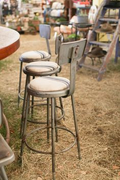 Industrial bar stools with French linen cushions.   http://annadeanstudio.com/a-guide-to-round-top-warrenton-antique-shows/