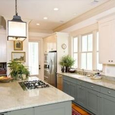 Contrasting upper and lower cabinets, lantern pendant, greenery accent color, grey-blue cabinets in this contemporary kitchen by CliqStudios