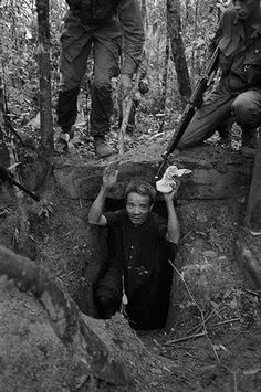 A Viet Cong soldier emerges from a spider hole