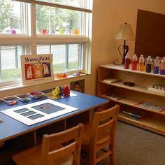 Reggio Emilia classroom.  Love the empty frame idea and colored water bottles