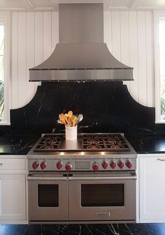 Black and white kitchen features white shaker cabinets paired with black soapstone countertops and backsplash.