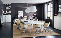 Ein Konferenzraum mit BEKANT Konferenztisch in Weiß mit Platz für 12 Personen und Konferenzstühlen mit Eichenfurnier und einer Sitzfläche mit Wollbezug in Grau