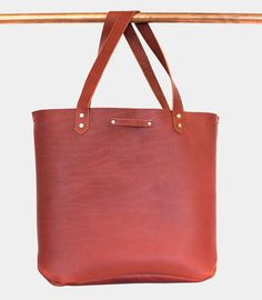 The Seanna leather tote has a raw leather interior and a clasp for closing. As it ages with use, it will start to take on its own personality.