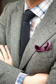 This dark grey and purple combo works together beautifully and the white shirt and boutonnière balances out the darker shades. And once again, mixing small patterns with larger ones works in favor of the checked pocket square against the plaid suit.