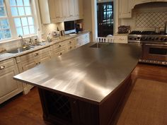 Stainless steel kitchen island with integral sink and curved front edge.