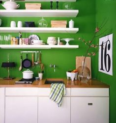 I am a big fan of open shelving in the kitchen.   I have done it before, and I would do it again.     Look at the great way that the white contrasts the green.   they chose two main colors and kept it simple.   but what a Punch of Fun!    you can do this in a small space and not feel claustrophobic.