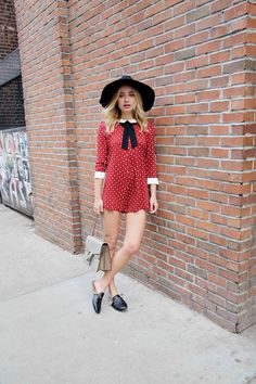 Sonya Esman wears a black hat with a red and white polka dot romper and loafers