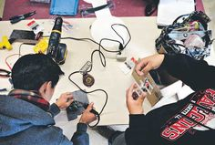 Tim Koh, 18, left, and Zenia Quintana, 18, work on engines for wind turbines at Skyline High School.