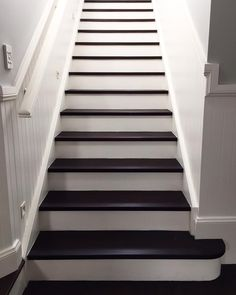 Staircase at the Seaforth project looking a bit like a baby grand. A beautiful effect achieved by staining the treads and painting the risers. #stairs #stairway #entry #wainscotting #hallway #interior #design