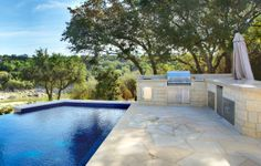 Spectacular outdoor kitchen and modern swimming pool designed by Cascade Custom Pools!