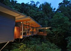This house constructed by Australian company MMP Architects was designed to fit seamlessly into a rainforest. Build on a slightly elevated platform, the house floats above the forest hill slope. The building consists of three large pavilions with large glass windows. It is made of high quality timber and partly of local stone, has solar power panels and is painted in subdued colors to dissolve into the natural background.