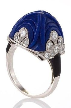 An Art Deco platinum and enamel ring with lapis lazuli and diamonds attributed to Marchak. Set with a carved sugar loaf cut lapis lazuli stone in a classic Art Deco motif and 22 round miligrain set diamonds, further enhanced by the enamel shoulders. Circa 1920's. #Marchak #ArtDeco #ring