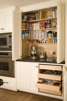 Custom Baking Center - this would work just as well for a regular cooking center with spices, pastas, seasoning mixes, blender, utensils, etc.  I love the giant doors that open up so you can see absolutely everything. Kitchen organization.