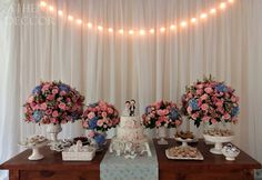 Detalhes de Casamento - Mesa de bolo e doces com ornamentos, peças de faiança para os doces. Ao fundo, cortina de voal e varal de luzes.