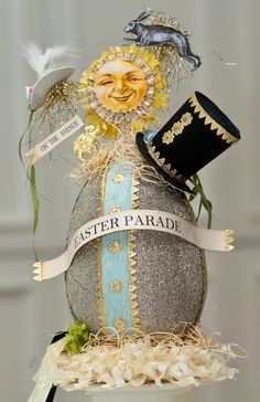 Easter Parade ~ glittered paper maché egg with top hat and Dresden foil gold borders and trims.