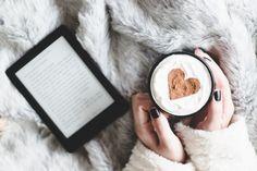 Foto tirada de cima na cama, com uma manta de pelúcia cinza, um e-reader (kobo glo hd) e um caneca com chocolate quente, chantilly e um coração feito de canela.