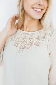 Loose fitting oatmeal colored top featuring a lace detailed front, bell sleeves, and delicate lace trim on the sleeves and hem.  Made from lightweight, semi sheer gauze fabric.  Wear with jeans, or tuck into a skirt!