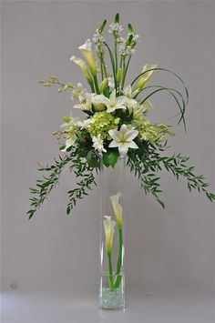 Tall, green and white centerpiece with calla lilies