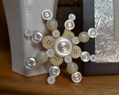 Button Snowflake Ornaments  4 wooden popsicle sticks   •various white, silver, gold, or cream colored buttons, in various sizes   •craft glue of your choice  Lay out buttons on stick; best to have opposite side of sticks match.  Leave one button off top a little so you can put string in hole to hang.